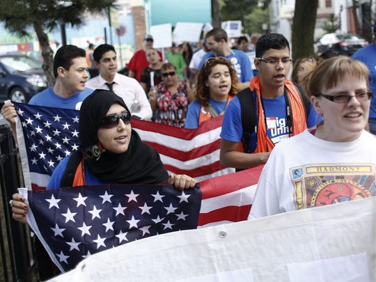 Sara Alshalali of Dearborn, center left, holds a flag and marches down the sidewalk during the Revive the Dream rally and march on August 24, 2013 at St. Anne's Church in Detroit.