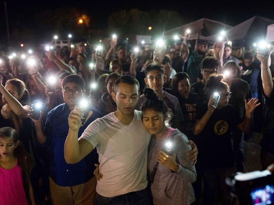 Members of the Sutherland Springs community hold up their cellphones Monday night during a prayer vigil to honor the 26 who where killed in the First Baptist Church shooting, Nov. 6, 2017.