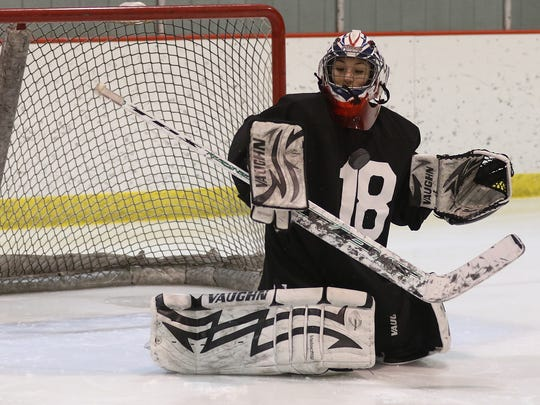 Wisconsin Rapids junior Chloe Kreuser looks to save the puck during a drill at Red Panthers practice at the South Wood County Recreation Center in Wisconsin Rapids, Friday, Jan. 29, 2016.