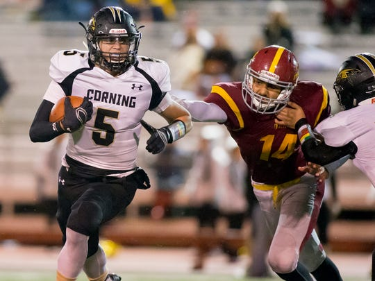 Corning's Jason Rodriguez gets running room to the outside as Ithaca's Harman Benipal is held up during a game last season.