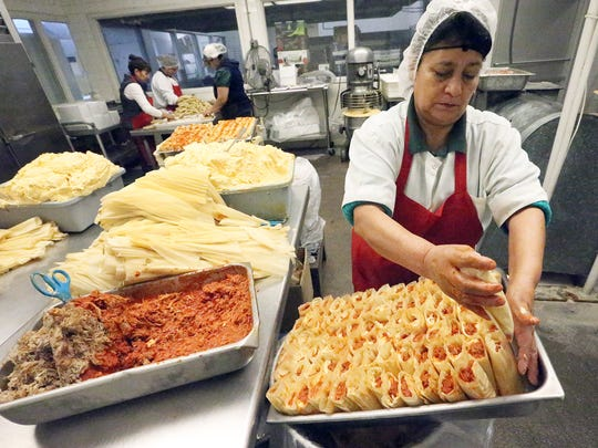 Tamal-maker Martha Hernandez on Friday fills a tray with freshly made red chile pork tamales before they are cooked in a steam bath for 2½ hours at La Tapatia, 8941 Old County Drive. The company makes about 250 dozen tamales daily from Thanksgiving to New Year's Day, said manager Carla Monsisvais. La Tapatia first opened in 1950.