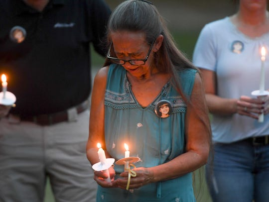 Cindy McDaniel bows her head in prayer during a candlelight