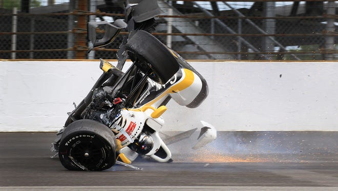 Josef Newgarden (21) of CHF Racing slides in his car inverted after he hit the wall and flipped coming out of turn one during practice for the Indianapolis 500 Thursday, May 14, afternoon at the Indianapolis Motor Speedway.