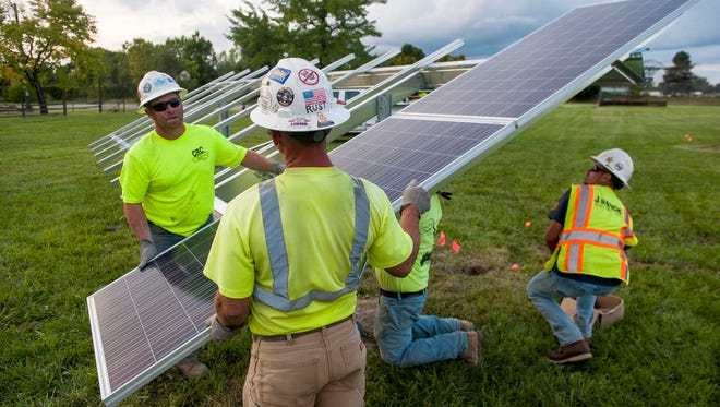 DTE Energy workers install a solar panel at the 10-acre O'Shea Playground in Detroit on Sept. 15, 2016.