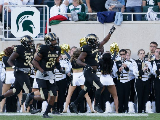Cornerback Darius Phillips (4) of the Western Michigan Broncos celebrates with defensive lineman DeShawn Foster (36)  and defensive back Stefan Claiborne (21) after scoring against the Michigan State Spartans on a 100 yard kickoff return during the second half at Spartan Stadium on September 9, 2017 in East Lansing, Michigan.