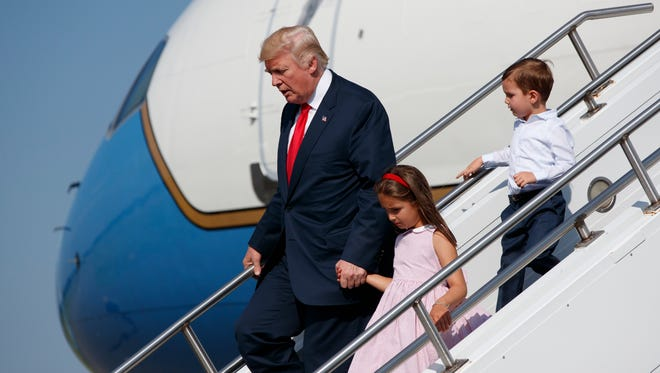 President Donald Trump walks down the steps of Air Force One with his grandchildren, Arabella Kushner, center, and Joseph Kushner, right, after arriving at Morristown Municipal Airport to begin his summer vacation at his Bedminster golf club, Friday, Aug. 4, 2017, in Morristown, N.J.