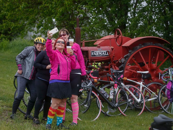 A group of cyclists take a group selfie near a Farmall