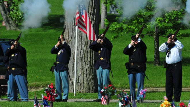 Honor guard members fire guns in salute during a Memorial Day service at the Veterans Field of Honor at Earlham Cemetery.