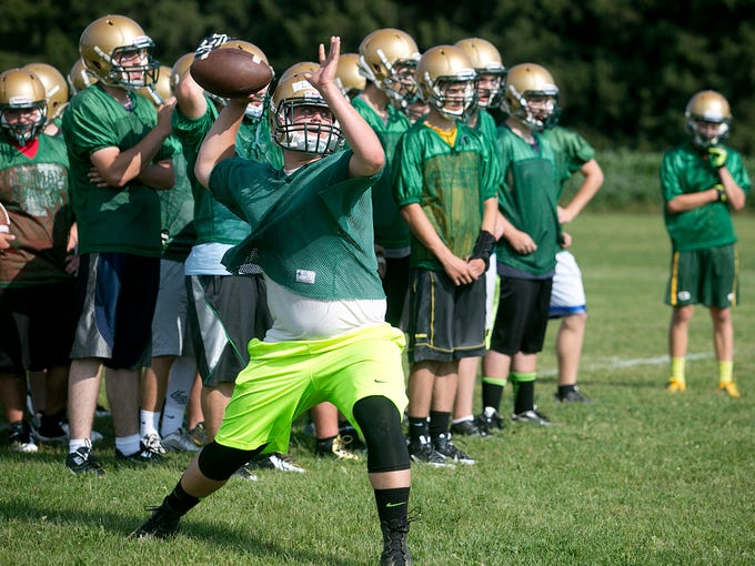 Colby quarterback Ryan Lynn looks to throw during football practice at Colby High School, Tuesday, August 5, 2014.
