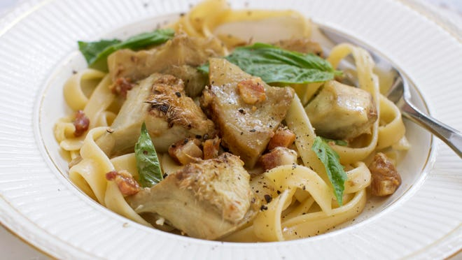 """This Sept. 15, 2014 photo shows fettuccine with sauteed artichoke hearts and pancetta in Concord, N.H. Often the autumn artichokes will have some brown spots, but that doesn't mean they're spoiled. In fact, these specimens are what the farmers call """"frost-kissed"""" and may be even more flavorful than their springtime cousins."""