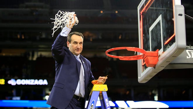 Duke Blue Devils head coach Mike Krzyzewski waves to the crowd after cutting down the net after defeating the Gonzaga Bulldogs in the finals of the south regional of the 2015 NCAA Tournament at NRG Stadium in Houston on March 29, 2015.