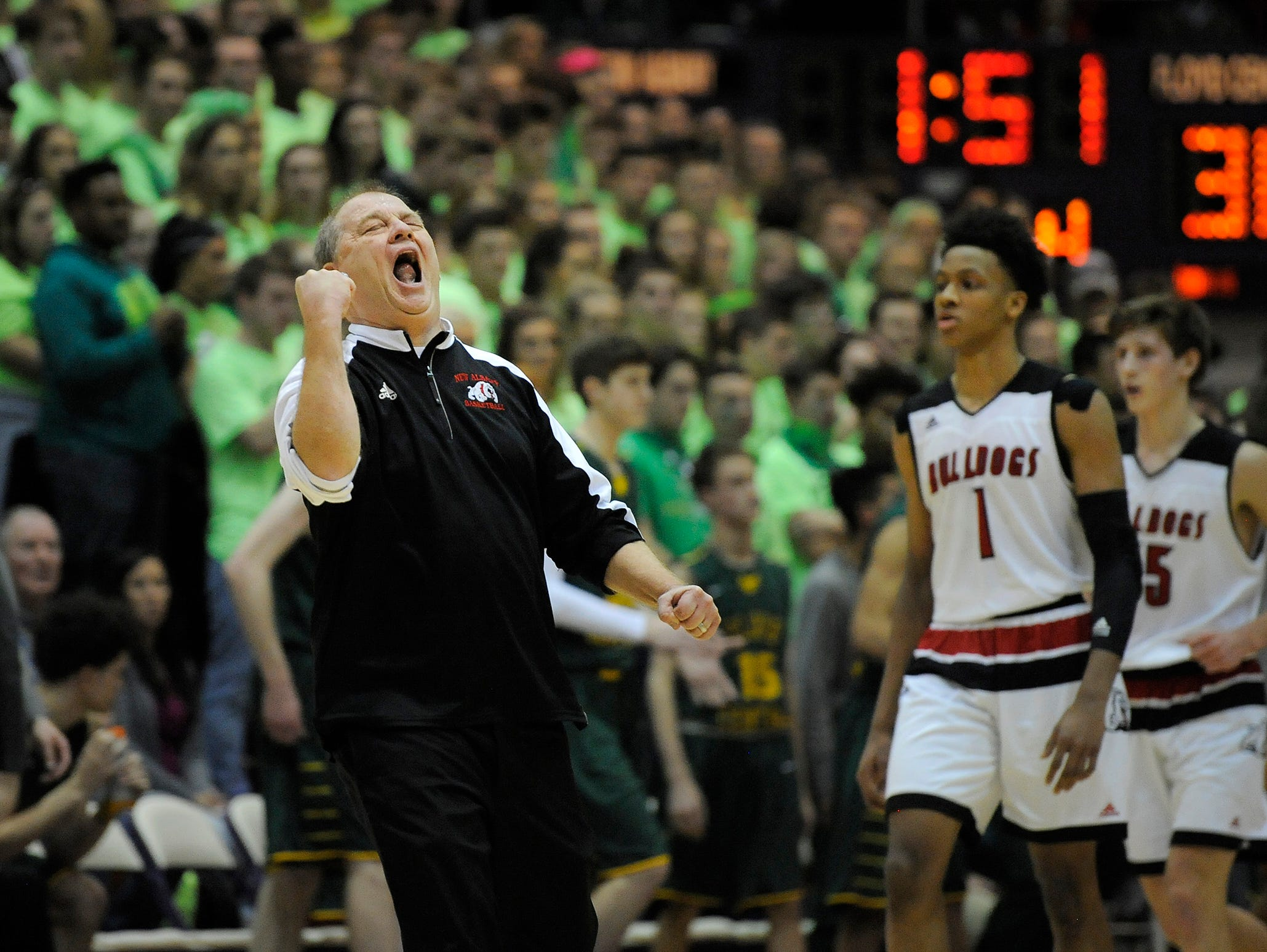 New Albany head coach Jim Shannon (left) celebrates a big shot with only minutes left of the 2017 Boys Class 4A Sectional 15 Final against Floyd Central at Seymour High School. New Albany won 54-38. (Photo by David Lee Hartlage, Special to The Courier-Journal) Mar. 4, 2017