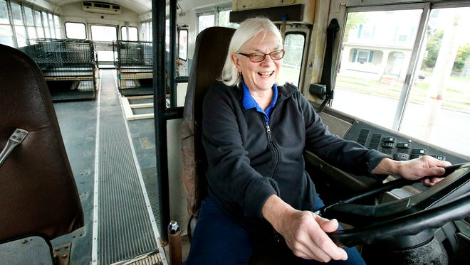 Elaine Walker sits in the driver seat of the Fire Emergency Rescue Waggin' — better known as the FER Waggin' — Thursday with several crates in the back of the bus. Walker, owner of Happy Tails Day Care and Pet Resort, will use the mobile shelter to assist at scenes where animals are displaced.