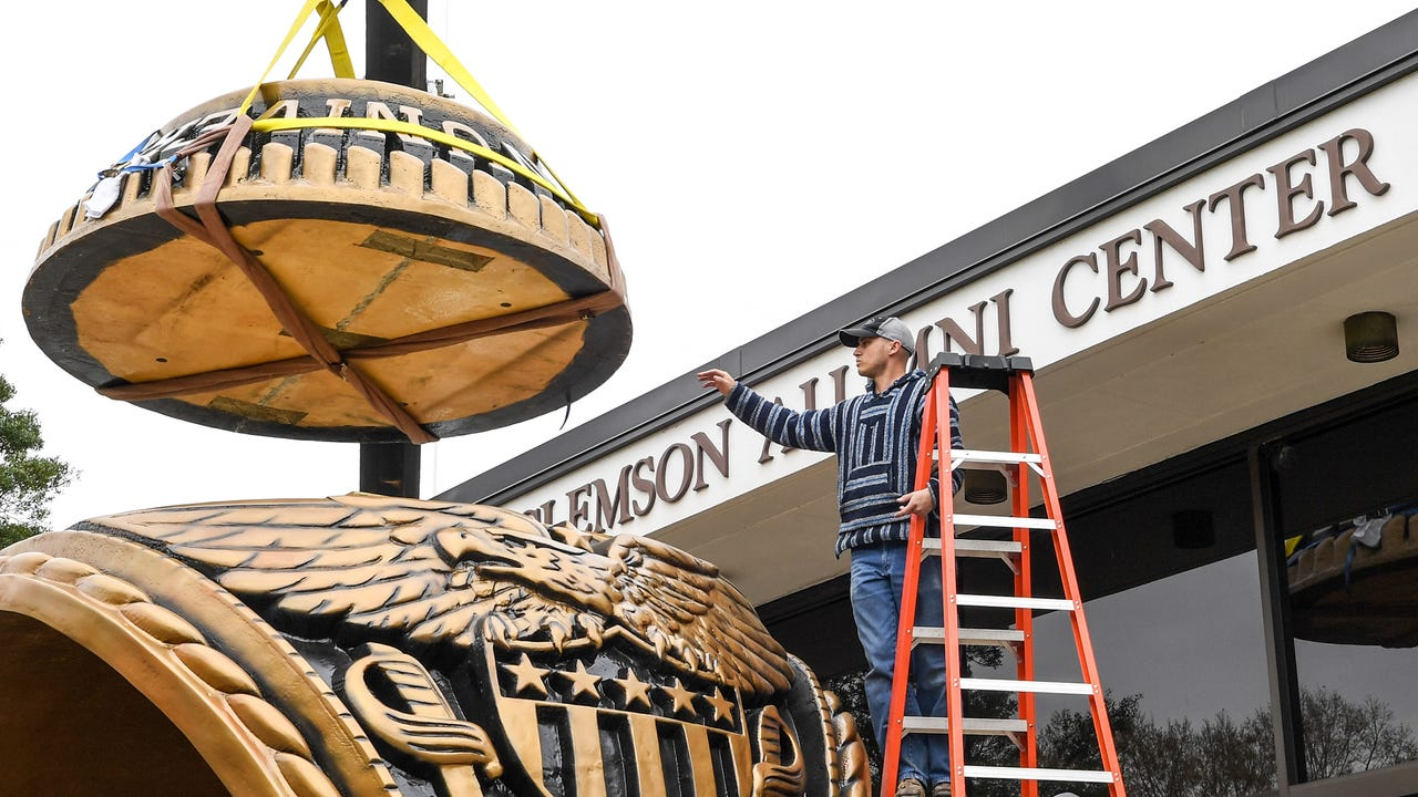 A crane lifts the 15-foot and 1,500-pound Clemson University alumni ring at the Clemson Alumni House on Monday.  The ring was originally made by Deep in the Heart Art Foundry in Bastrop, Texas, with wood and paint, was refurbished with steel.