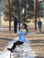 Dayanara Neibauer, 7, of Fond du Lac, enjoys the warm weather Friday while riding the zipline in Lakeside Park. Temperatures topped off in the upper 50s which is 25 degrees above normal for this time of year.