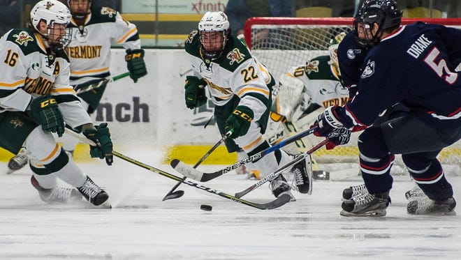 From left, UVM's Derek Lodermeier and Alex Esposito try to clear the puck  as UConn's David Drake tries to keep it on the Catamount's side of the ice during their Hockey East men's hockey match up at Gutterson Fieldhouse Tuesday night, Nov. 21, 2017.