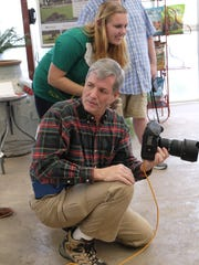 Staff Sgt. (Sel) Taylor Inhoff assists photographer Ken Pruett during the Dyess We Care Team's annual Pet Pics With Santa project, which raised almost $750 for the Taylor Jones Humane Society.