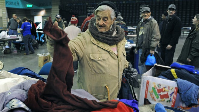 Dolores Felten sorts through a table full of coats at the Project Homeless Connect inside the Reno Events Center in 2009. The event provides homeless individuals and families with free services such as medical care, social services, housing information and quality of life services such as haircuts and massages.