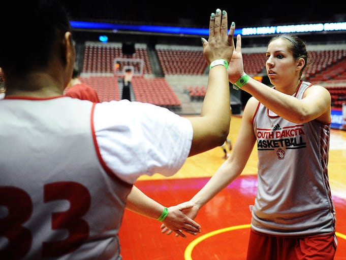 USD's Lisa Loeffler, right, gets high fives from teammates Polly Harrington (33) and Bridget Arens during a practice prior to the first round of the NCAA Women's Basketball Tournament on Friday, March 21, 2014, at the Hilton Coliseum in Ames, Iowa.