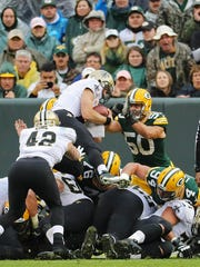 New Orleans Saints quarterback Drew Brees (9) dives over the goal line for aq touchdown with Green Bay Packers inside linebacker Blake Martinez (50) trying to stop him  during the Green Bay Packers 26-17 loss to the New Orleans Saints at Lambeau Field in Green Bay, Wisconsin, Sunday, October 22, 2017.
