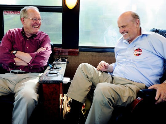 Sen. Lamar Alexander, left, laughs with former Sen. Fred Thompson while traveling on Alexander's campaign bus in Middle Tennessee on Aug. 5, 2014.