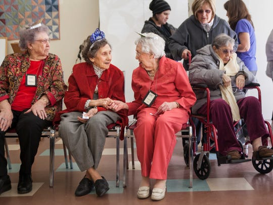 Dot Harvey, center left, holds hands with Laura Luzaich, 94, as they sit beside Daisy Curry, 95, left, during the Staunton Senior Center's celebration of members over 90 years old on Wednesday, March 18, 2015.