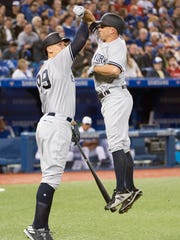 Mar 29, 2018; Toronto, Ontario, CAN; New York Yankees left fielder Brett Gardner (11) celebrates hitting hits a home run with right fielder Aaron Judge (99) in the seventh inning during the Toronto Blue Jays home opener at Rogers Centre.
