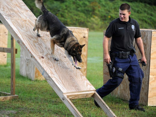In this Oct. 16, 2012, file photo, Hattiesburg Police Officer Benjamin Deen runs his canine, Tomi, through an obstacle during a training exercise at the Hattiesburg Police Department's K-9 training course. Deen and fellow officer Liquori Tate were fatally shot Saturday, May 9, 2015.