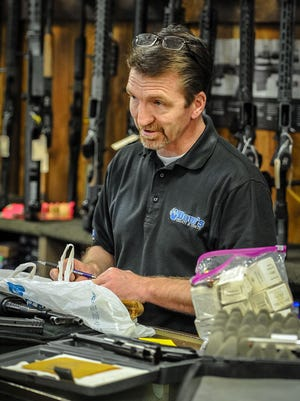 Dave Larsen speaks with a customer about selling firearms at Doug's Shoot'n Sports in Taylorsville on Tuesday, April 17, 2018.