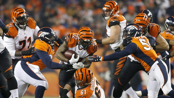Cincinnati Bengals running back Jeremy Hill, center, looks for running room against Denver.