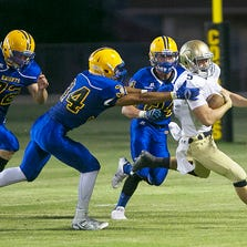 Yuma Catholic's Jager Cleary tries to breaks away from Tempe Prep's Zachariah Brittain during Friday night's game at Phoenix Arizona Lutheran.
