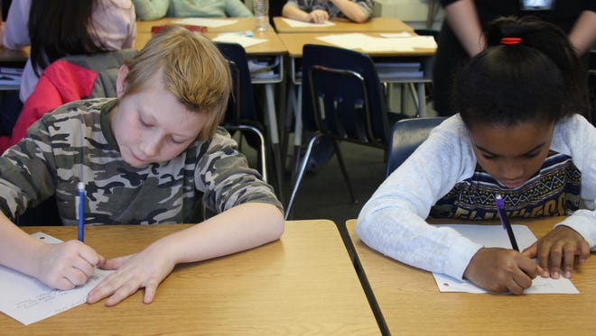 Hamilton fourth-graders William Kotrys and Adrianne Davis work on their letters.