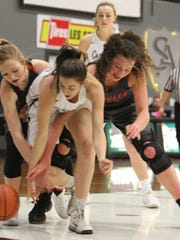 Salem Academy's Kara Standridge fights for the ball with two players from Santiam Christian on Friday, Feb. 23, 2018.