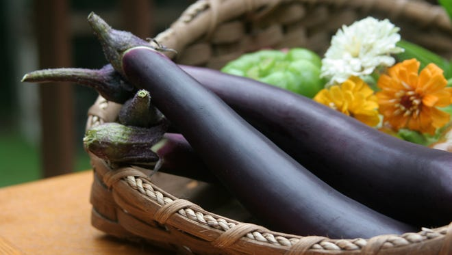 File picture -- Eggplants and flowers in a basket.