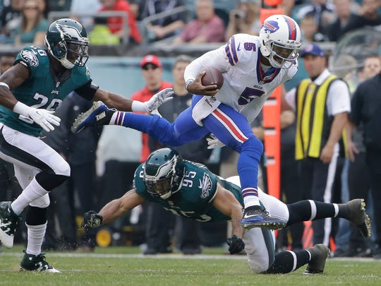 Buffalo Bills' Tyrod Taylor (5) leaps past Philadelphia Eagles' Mychal Kendricks (95) and Walter Thurmond (26) during the first half of an NFL football game, Sunday, Dec. 13, 2015, in Philadelphia.