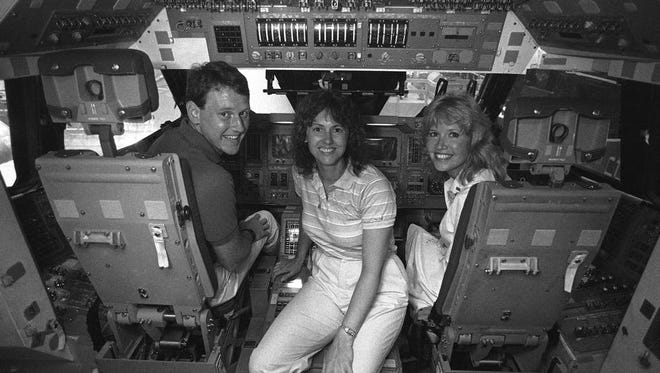Robert Foerster of West Lafayette, Christa McAuliffe of Concord, New Hampshire, and Kathleen Beres of Baltimore, Maryland, pose in July 1985 in a space shuttle mockup at the Johnson Space Center in Houston. They were three of 10 finalists in NASA's Teacher in Space Project.
