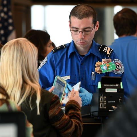 A TSA Officer Mandarano checks in a passenger at...