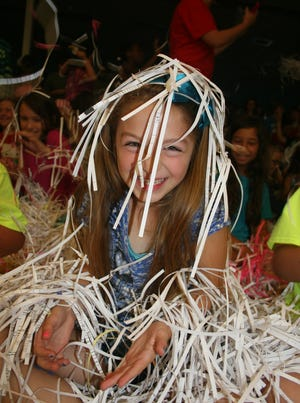 Mikayla Peterson, a third-grader, gets showered with confetti during Holley Navarre Intermediate School's end-of-the-year celebration Friday.