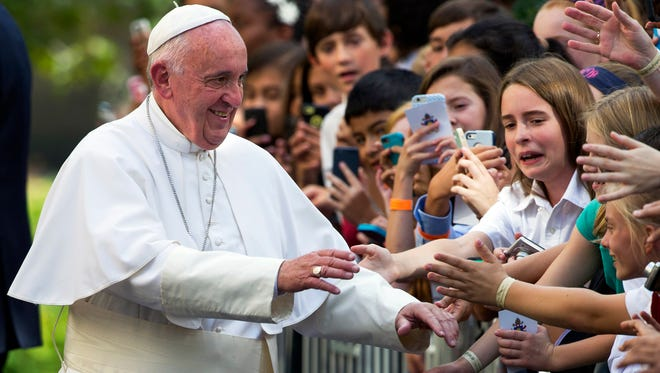 Pope Francis greets schoolchildren as he departs the Apostolic Nunciature, the Vatican's diplomatic mission in the heart of Washington, en route to Andrews Air Force Base on Sept. 24, 2015.