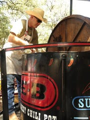 "photos by Thomas Metthe/Reporter-News Brad Birchun, with the Taylor County Sheriff's Department, stirs the ""world's largest chili pot"" during the 34th Annual Chili Super Bowl and Cook-off on Sept. 5, 2015, in Buffalo Gap."