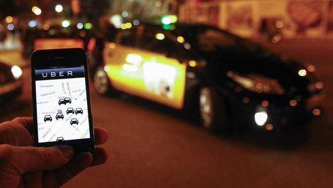 The Uber app is seen on a smartphone past cabs waiting for clients near the Sagrada Familia in Barcelona.