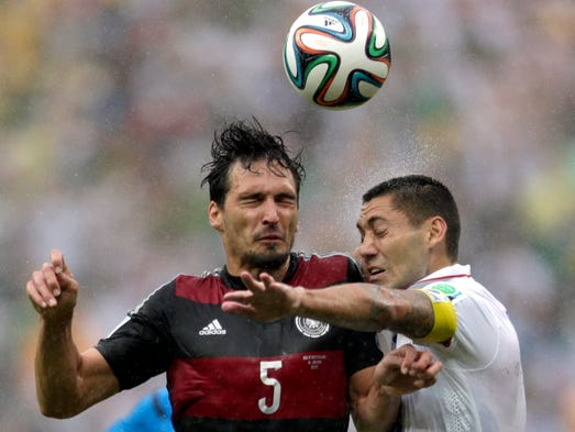 Germany's Mats Hummels heads the ball with United States' Clint Dempsey during the group G World Cup soccer match between the United States and Germany at the Arena Pernambuco in Recife, Brazil, Thursday, June 26, 2014. (AP Photo/Julio Cortez)