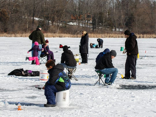 Youngsters and their parents take to the ice during the Take a Kid Ice Fishing clinic at School Section Lake in Dousman on Saturday, Jan. 20, 2018. The annual event is sponsored by the Sons of the American Legion Post 189 of Watertown, which provide gear, guides, bait, food and drinks as they introduce new anglers to the sport.