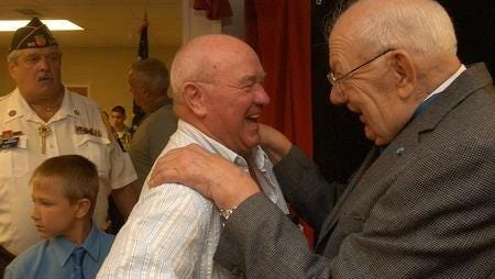 Hector Cafferati Jr. (right) during a ceremony dedicating the elementary school that bears his name. The event was in April 2006. The medal of honor winner died this week.