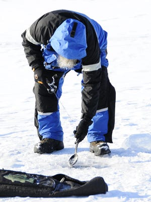 Gary Newell, of Lexington, scoops ice chunks while ice fishing at the Lexington Harbor.