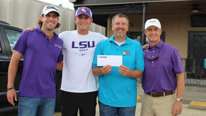 Andrew Loupe (left), Smylie Kaufman (2nd from left) and David Toms (right) offer a $100,000 check to Jeff Taylor to help flood victims in South Louisiana.