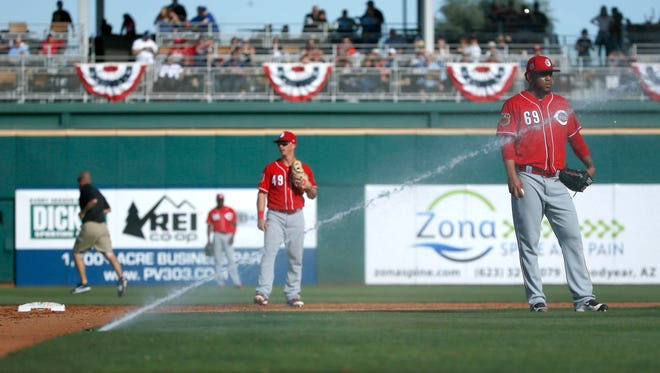 Reds relief pitcher Ariel Hernandez walks off the mound as the field sprinkler system start up unexpectedly.