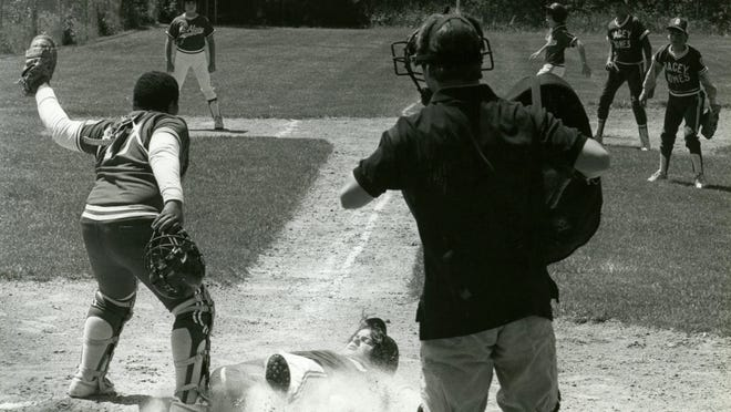 A runner slides in safe at home in June 1986 Barnstable Little League action.