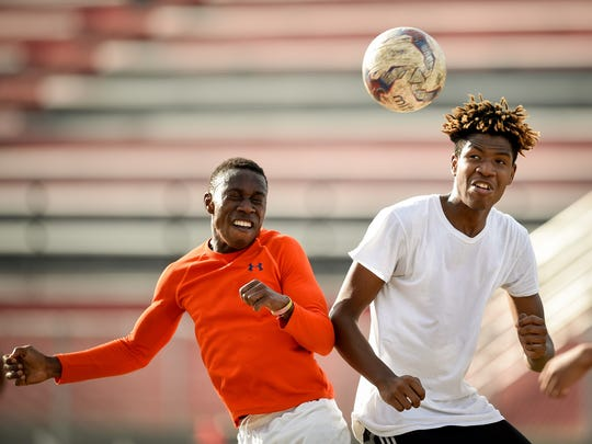 Fernando Buhendwa, left, and Nicholas Booker, right, run drills during practice at Pearl-Cohn High School in Nashville, Tenn., Tuesday, March 28, 2017.