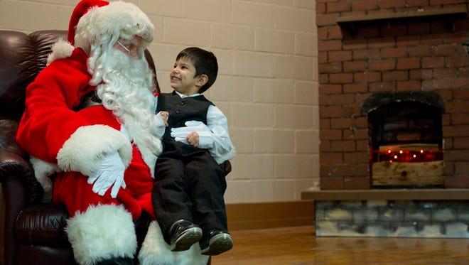 Landon Castillo,4, sits on Santa's lap during a Winter Wonderland community event Thursday, Dec. 17, 2015 at East Shore Leadership Academy in Port Huron.